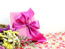 Pink gift box with ribbon and flower bouquet. On printed fabric background Stock Image