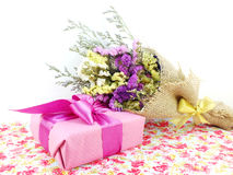 Pink gift box with ribbon and flower bouquet. On printed fabric background Royalty Free Stock Photography
