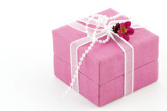 Pink gift box with a ribbon and a little flower. Beautiful pink gift box with a ribbon, a little flower and pearls Stock Photo