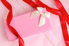 Pink gift box with ribbon on pink background. Pink gift box with red ribbon on pink background Royalty Free Stock Images