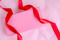 Pink gift box with ribbon on pink background. Pink gift box with red ribbon on pink background Royalty Free Stock Photo