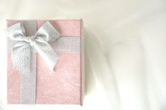 Pink gift box with silver ribbon. Top view of pink gift box with silver ribbon on white Stock Image