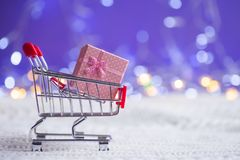 Pink gift box in small supermarket trolley on white knitted fabric on purple background with warm bokeh. New year banner with empty space. Concept of female or stock images