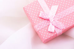 Pink gift box tied with satin ribbon with bow on delicate white fabric background, romantic, valentine, mother`s day, Christmas Stock Image
