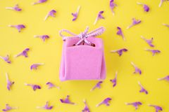 Pink gift box on a yellow background with flowers. Festive concept.  Flat lay, top view stock image