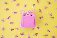 Pink gift box on a yellow background with flowers. Festive concept.  Flat lay, top view royalty free stock photo