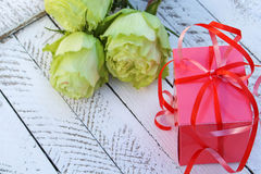 Pink gift box and yellow-green roses on wooden background Royalty Free Stock Photo