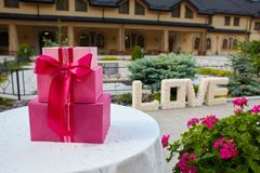 Pink gift boxes on a circle white table outdoors. Word Love made of paper flowers outdoors. royalty free stock images