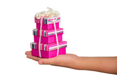 Pink gift boxes in hand. Giving away, thanks giving - seasonable present in stretched hand: three gift boxes bound up by a festive ribbon and topped with a bow Royalty Free Stock Photos
