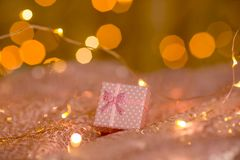Pink gift on a coral background with blurred lights of a garland. royalty free illustration