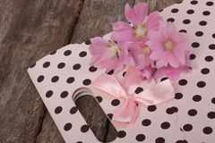 Pink gift paper bag and wild mallow flowers Stock Photos