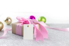 Pink giftbox and card. Beautiful giftbox with pink ribbon and blank tag for happy celebration royalty free stock photo