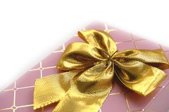 Pink giftbox with golden knot. Good quality close up photo of a graceful gift: soft pink color giftbox, fine golden metallic pattern with elegant ribbons and Stock Photo