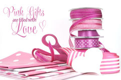 Pink Gifts are filled with Love, greeting with polka dot and plain ribbons, scissors, and wrapping paper. For Valentines Day, Mothers Day, birthdays, wedding or Royalty Free Stock Photos