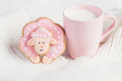 Pink gingerbread sheep with cup of milk on white knitted backgro. Und. Pastel colored stock photo