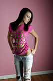 Pink girl. Model posing in pink shirt on pink background Royalty Free Stock Photo