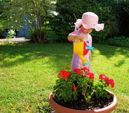The pink girl. Little girl in pink suite watering flowers in the garden Royalty Free Stock Photo