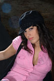 Pink girl with cap. The model is wearing a pink shit and a black cap. The shirt is slightly unbuttoned Stock Photography