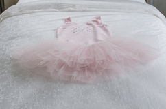 Pink girl's dress on bed Stock Photo