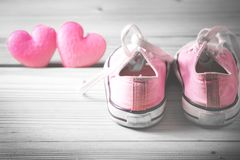 Pink girl sneakers with pink hearts. On a wooden floor, selective color Stock Photo