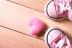 Pink girl sneakers with pink hearts on a wooden floor Stock Photos