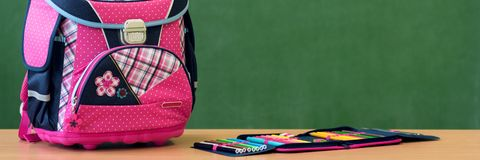 Pink girly school bag and pencil case on a desk against greenboard. First day of school. Pink girly school bag and pencil case on a desk against greenboard stock photography
