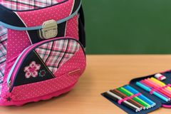 Pink girly school bag and pencil case on a desk against greenboard. First day of school concept royalty free stock images