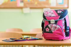 Pink girly school bag and pencil case on a desk in an empty classroom. First day of school concept Royalty Free Stock Photos