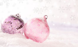 Pink glass Christmas baubles. Pink Christmas baubles on a snow background with snowflakes and blurred light effects Royalty Free Stock Photos