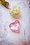 Pink glass heart with dried rose, aged stylized photo Stock Images