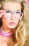 Pink glasses. Portrait of a charming blonde woman in pink spectacles posing in studio over pink background Stock Photo