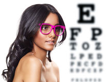 Pink glasses on beautiful tanned woman. Beautiful tanned woman with long curly hair wearing pink glasses on eye test background Royalty Free Stock Images