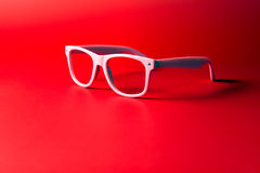 Pink glasses. Close up of pink glasses on red background stock photo