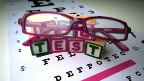 Pink glasses falling next to blocks spelling out eye test Stock Photography