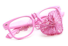 Pink Glasses and Heart Necklace. Pink glasses and heart shaped wired pendant on ball chain, isolated on white background Royalty Free Stock Photography