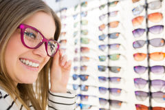 Pink glasses. A photo of young woman at the optician's trying on pink glasses Royalty Free Stock Image