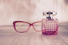 Pink glasses pink perfume. Small fragrance bottle near pink glasses concept Royalty Free Stock Photos