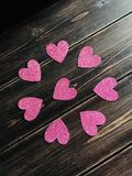 Pink glitter hearts on a wooden background. Valentine's Day concept. stock photos