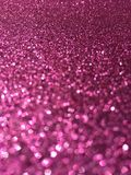 Pink glitter sparkle focus background. Close up of pink shimmery glitter with narrow depth of field, showing blurry glitter in the front and clear sharp glitter Stock Photography
