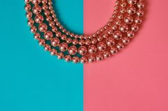 Pink gold beads on pink blue background. Pink gold beads lay on pink blue background Royalty Free Stock Photos
