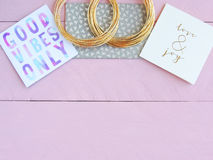 Pink and gold desktop with greeting cards and golden bracelets Stock Photo
