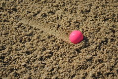 Pink golf ball in a bunker royalty free stock images