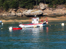 Pink granite coast and fishing boat. Royalty Free Stock Photo