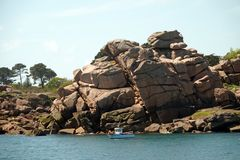 Pink Granite rock formations near Perros Guirec in Brittany. Crab and lobster fishing in small boat. Côte de Granit Rose is one of the most beautiful stock photos