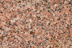 Pink granite tile pattern. Polished surface stone with rosy black hues. macro view Royalty Free Stock Image