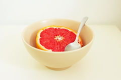 Pink grapefruit in a bowl with spoon Stock Image