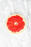 Pink grapefruit on gray marble Royalty Free Stock Image
