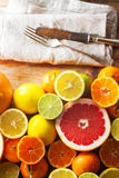Pink grapefruit and other citrus fruit against wooden background Stock Photo