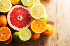 Pink grapefruit and other citrus fruit against wooden background Royalty Free Stock Photos