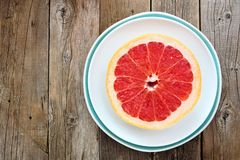 Pink grapefruit on plate with rustic wooden background Royalty Free Stock Images